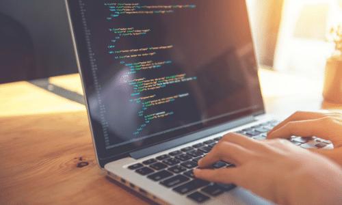 Developer typing code on laptop
